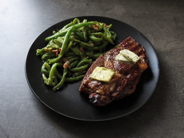 T-Bone-Steak mit Speckbohnen.