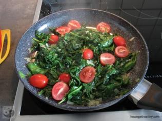 Rührei mit Spinat und Tomaten in der Pfanne