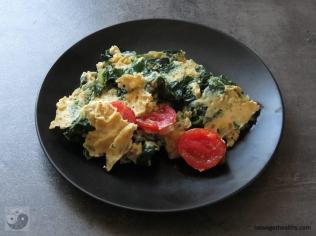 Rührei mit Spinat und Tomaten auf dem Teller