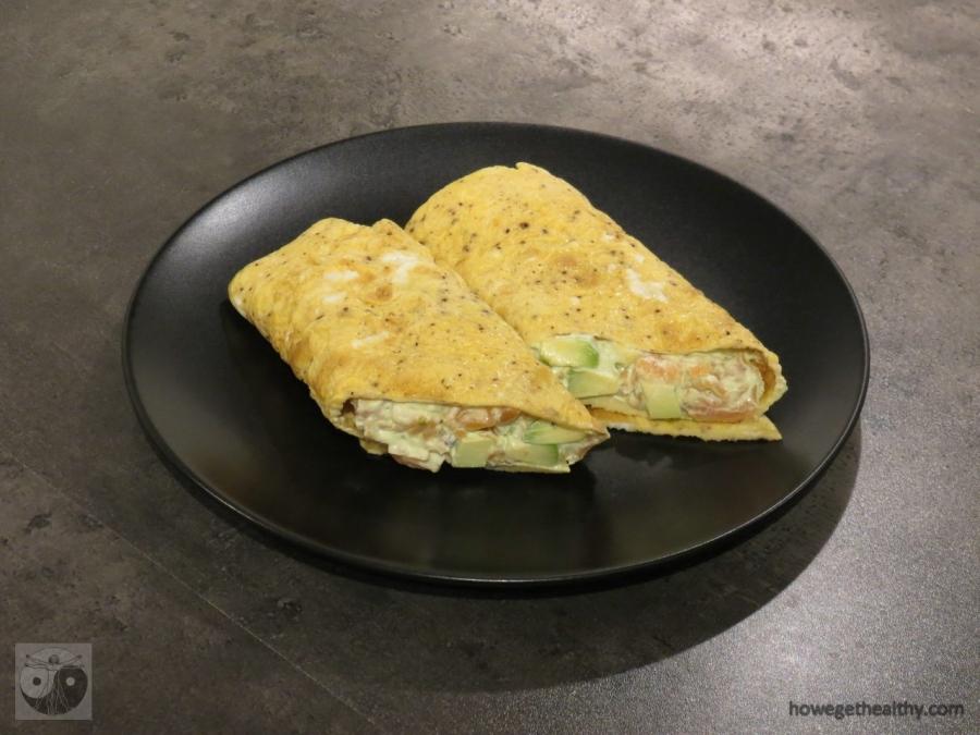 Frühstücksrolle mit Lachs-Avocado-Mayonnaise auf dem Teller